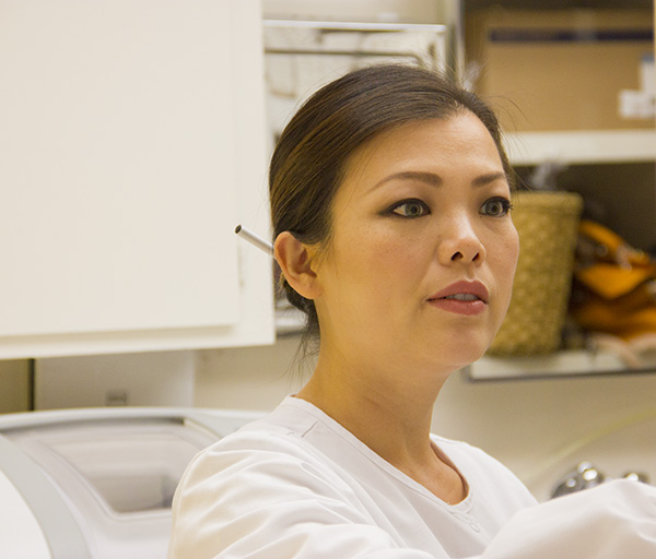 Katelyn Du DDS examining tooth. Learn more about the practice.